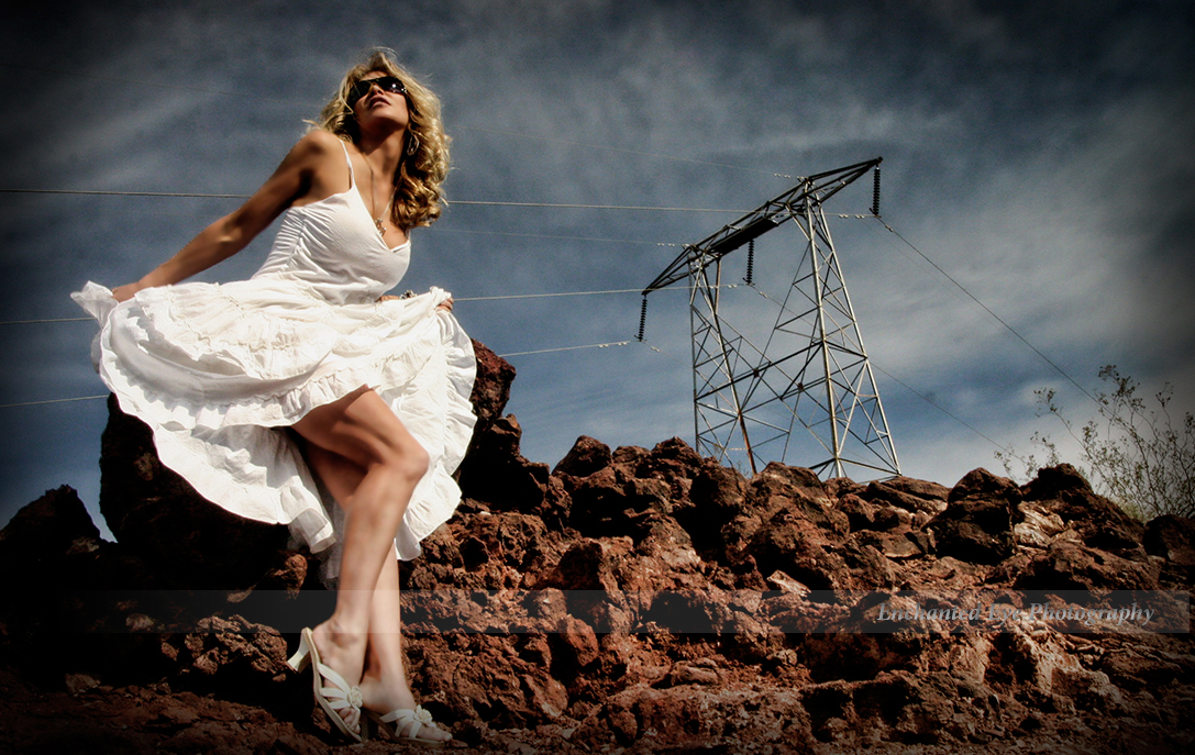 Fluffy white dress on sexy woman with sky, power lines in red volcanic rocks.